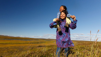two girls in traditional garments, in a field, one is giving the other a piggy back ride, both are smiling and looking into the distance